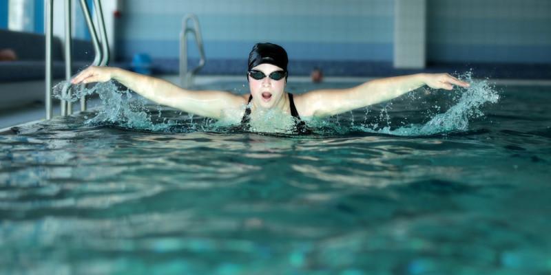 Junge Sportschwimmerin schwimmt im Butterfly-Stil mit ausgebreiteten Armen auf den Betrachter zu.