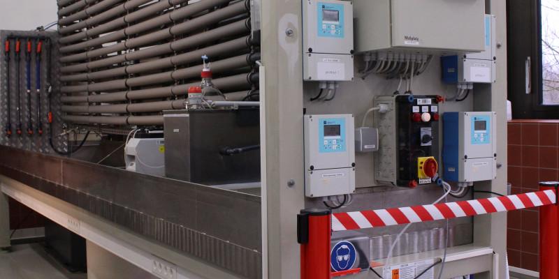 Teststand für Desinfektionsmittel. Im Vordergrund rechts elektronische Schalt- und Steuereinheiten, im Hintergrund links wärmeisolierte Wasserrohre der Teststrecke.