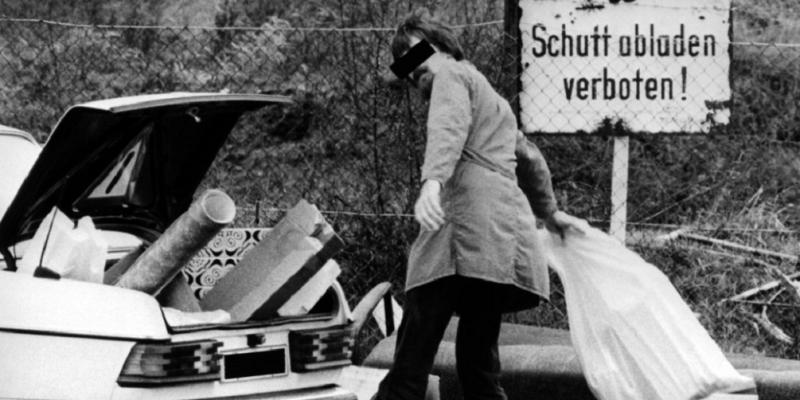 """ein Mann lädt an einem Schild """"Schutt abladen verboten"""" Müll aus seinem Autokofferraum aus"""