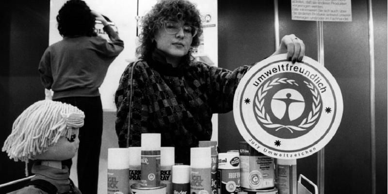 Eine Frau hält das Umweltzeichen in die Kamera, vor ihr auf einem Tisch viele Produkte, die das Umweltzeichen tragen, zum Beispiel Rasierschaum-Flaschen.