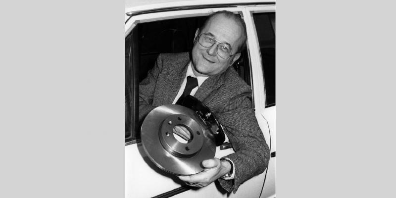 Von Lersner lehnt sich aus einem Autofenster und hält asbestfreie Bremsbeläge in die Kamera