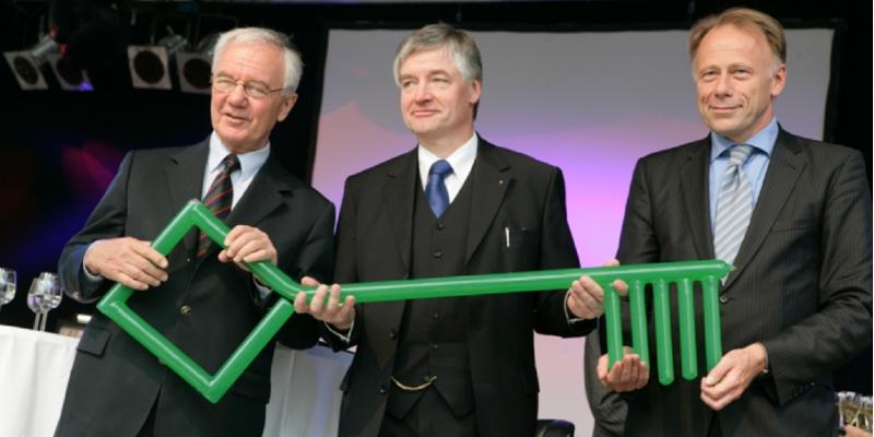 Gruppenfoto: drei Männer in Anzug und Krawatte halten einen riesigen grünen Schlüssel, im Hintergrund Sektgläser