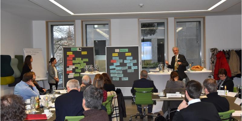 Burkhard Huckestein spricht vor Teihnehmenden der Veranstaltung, auf einer Flipchart Zettel mit Stichworten