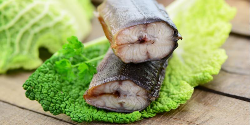 Zwei Stücken Aal auf einem Wirsingkohlblatt liegen auf einem Holztisch, im Hintergrund Messer und Gabel