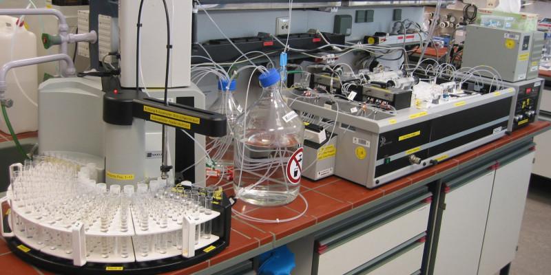 In einem Labor stehen auf einer Arbeitsplatte Analysegeräte und Behälter mit Flüssigkeiten