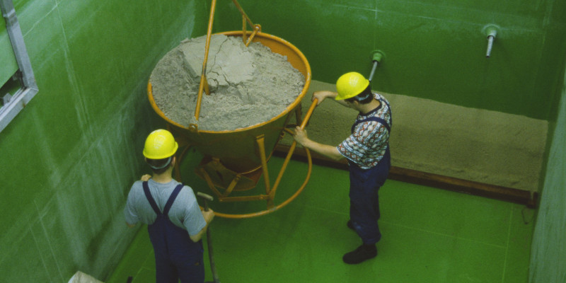 Zwei Männer mit Arbeitskleidung und Sturzhelmen stehen in einem tiefen grünen Teichbehälter mit einem von oben herabhängenden, trichterförmigen Gefäß mit Sand