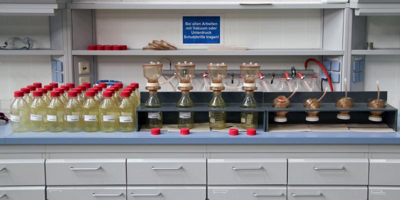 in einem Labor stehen auf einer Arbeitsplatte viele durchsichtige Gefäße mit roten Deckeln, an der Wand hängt ein Schild: Bei allen Arbeiten mit Vakuum oder Unterdruck Schutzbrille tragen!