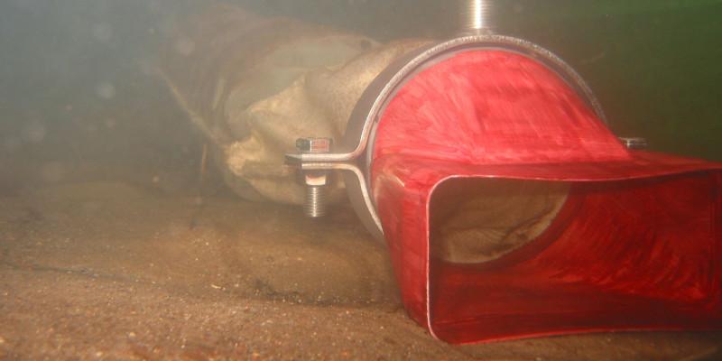 Unterwasseraufnahme: auf dem sandigen Grund liegt Röhre aus einem ausgestieften Fliesstoff