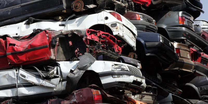 verschrottete Altautos mit demontierten Reifen auf einen Haufen getürmt