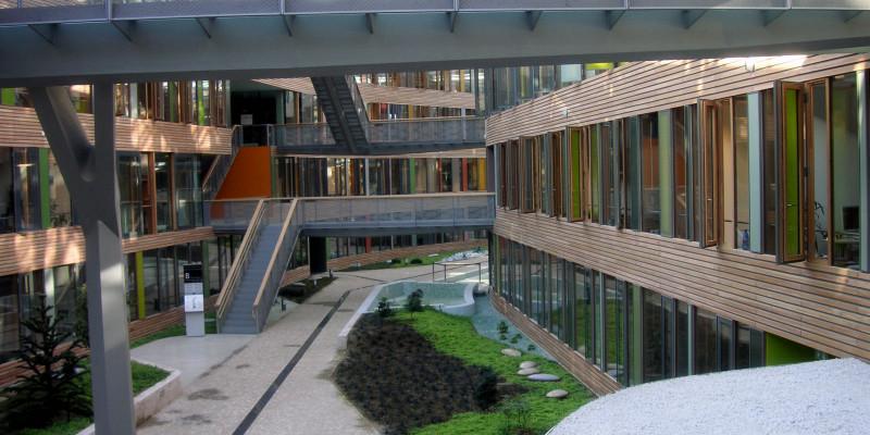 langgestreckter Innenhof mit Glasdach, Verbindungsbrücken zwischen dem linken und rechten Gebäudeteil, Anpflanzungen und Wasserbecken