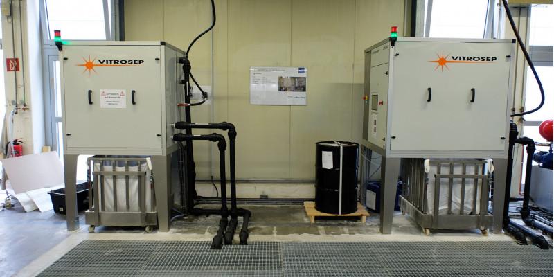 teschnische Anlage in einer Werkshalle aus zwei Boxen, aus denen Rohre in eine Gitterabdeckung im Fußboden führen