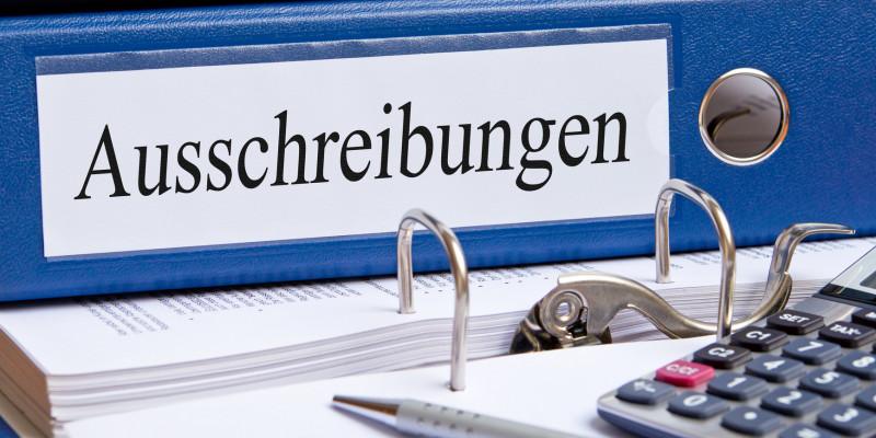 """auf einem Schreibtisch liegen ein Ordner mit der Aufschrift """"Ausschreibungen"""", ein Taschenrechner und ein Stift"""