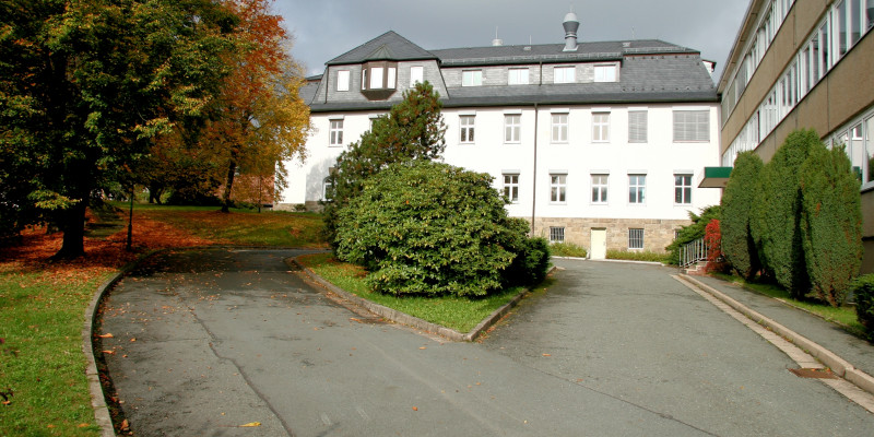 White, four-storey historic building with drive through a landscaped area, a three-storey annex on the right