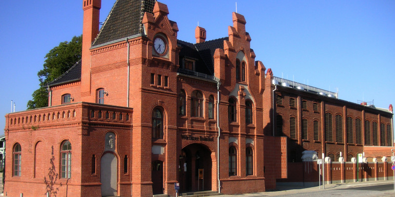 Small, old red-brick train station building with spire and gable
