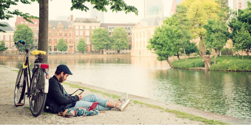 ein junger Mann sitzt in der Stadt an einem Fluss unter einem Baum und schaut auf sein Tablet mit Kopfhörern im Ohr. Am Baum lehnt sein Fahrrad.