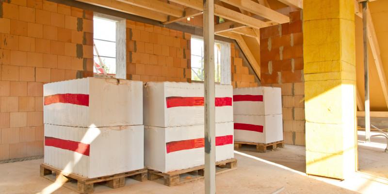 ein Gebäude im Rohbau von innen, auf Paletten stehen Baumaterialien