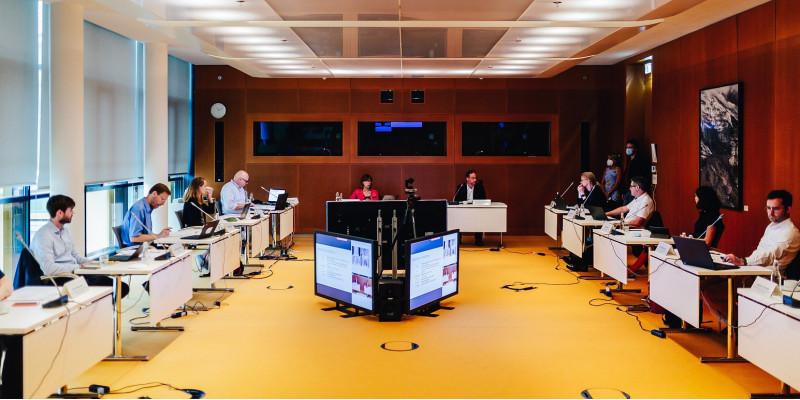 10 Personen sitzen in einem Saal an im Kreis angeordneten Tischen mit Laptops und Mikrofonen, in der Mitte große Bildschirme