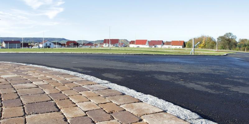 """asphaltierte Straße und gepflasterter Weg, im Hintergrund ein Neubaugebiet """"auf der grünen Wiese"""""""