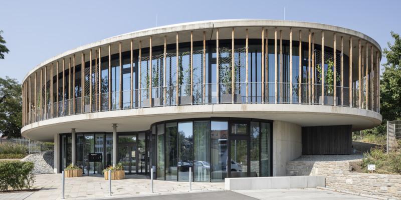 modernes, 2-geschossiges, rundes Gebäude aus Beton, Glas und Holz