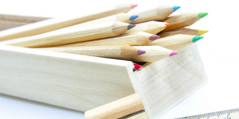 unlackierte Holz-Buntstifte in einem Holzkästchen, daneben ein Anspitzer aus Holz und ein Lineal