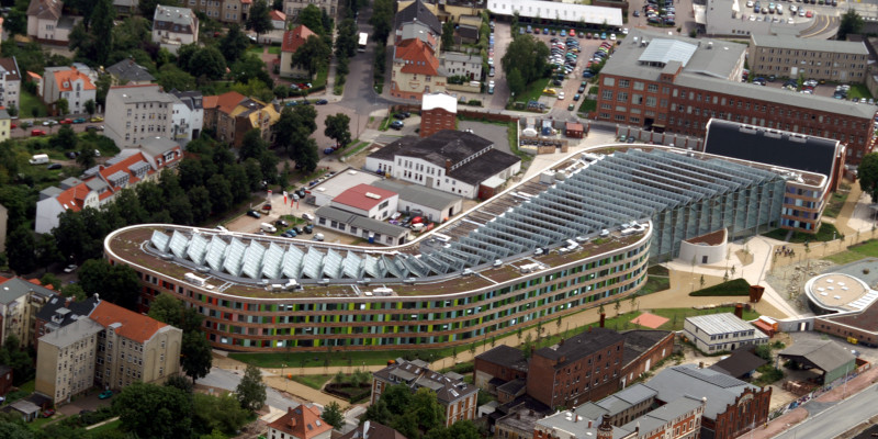 Das schlangenförmige UBA-Dienstgebäude in Dessau-Roßlau von oben fotografiert, zu sehen ist die Fassade aus Holz und bunten Glasscheiben und die schräg aufgestellten Solarzellen auf dem gesamten Flachdach