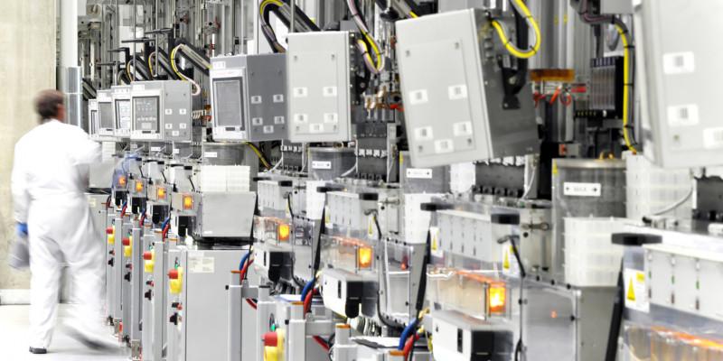 ein Mitarbeiter in einem weißen Schutzanzug in einem Betriebsraum mit vielen elektrischen Geräten, Kabeln und Kästen, die an der Wand stehen oder aufgehängt sind