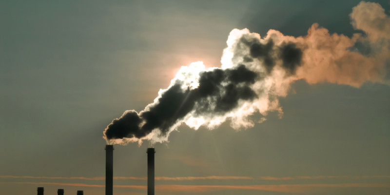 Smoke from chimney blocking the sun, hazy grey sky in background