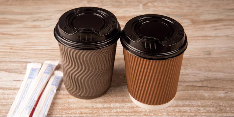 """zwei """"Coffee to go""""-Becher auf einem Tisch, daneben zwei Papiertütchen mit Zucker"""
