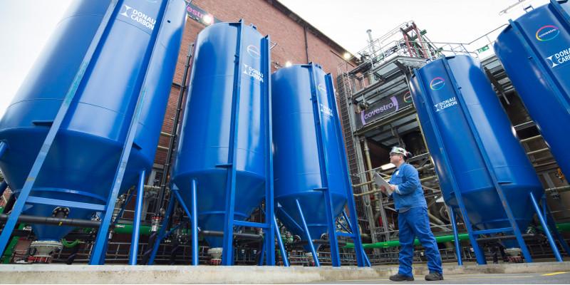 Mann in Arbeitskleidung vor 5 riesigen blauen Tanks vor einer Werkhalle