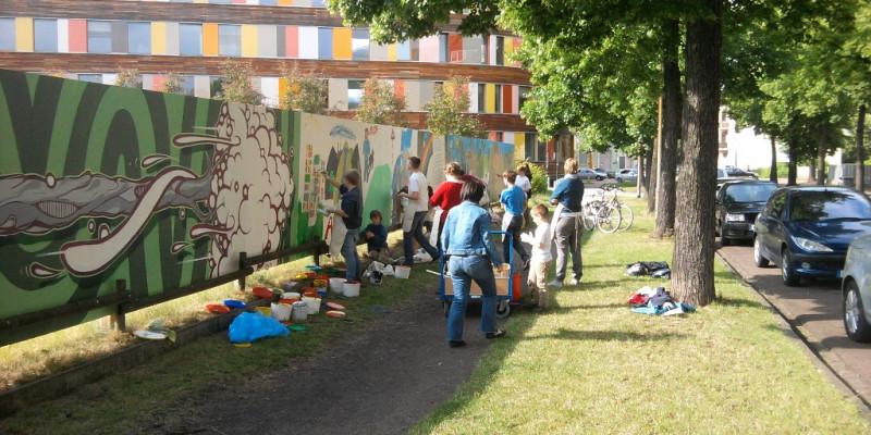 Kinder und Jugendliche malen mit Betreuerinnen den aus einer blickdichten Holzwand bestehenden Bauzaun mit bunten Bildern an