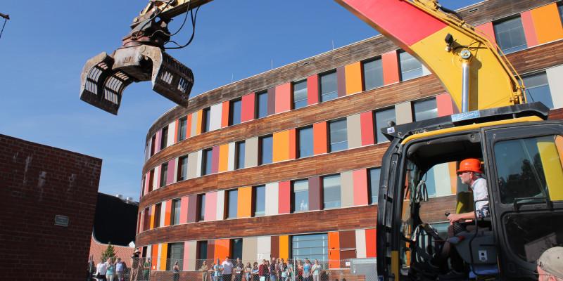 UBA-Präsident Flasbarth sitzt vor dem Dienstgebäude in Dessau-Roßlau in einem Bagger, um eine alte Wand aus Ziegeln einzureißen, Menschen am Bauzaun schauen zu