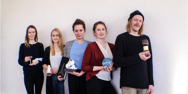 vier junge Frauen und ein junger Mann mit Trophäen in der Hand an eine Wand gelehnt