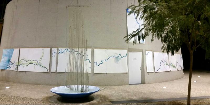 Kunstinstallation im Vorraum des UBA Dessau: über einer großen Schale hängt ein Vorhang aus Schnüren, an dem Wasser herunterläuft, man erkennt die Silhouette eines Menschen