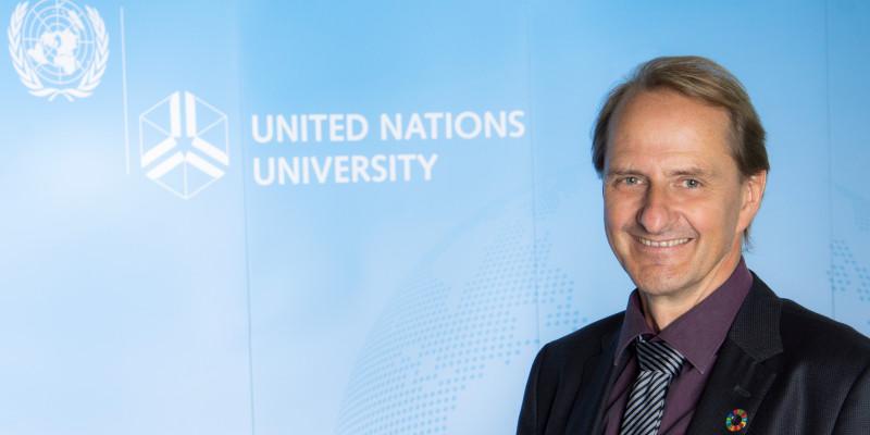 """Dirk Messner vor einem blauen Aufsteller mit der Aufschrift """"United Nations University"""" und dem Logo der Vereinten Nationen"""