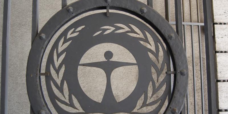 Hohes, schwarzes Eingangstor aus Metallgitter mit dem Umweltengel
