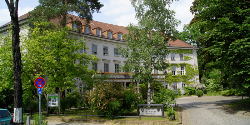 """Three-storey historic building with entrance portal, with balcony and flower boxes above, gabled roof with many small dormers. At the front a square with trees, bushes, a drive and sign which reads """"Umweltbundesamt"""""""