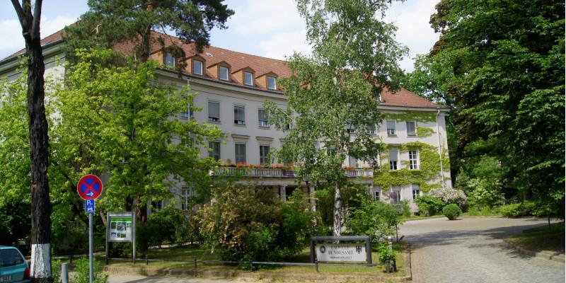 """dreistöckiger Altbau mit Eingangsportal, auf dem sich ein Balkon mit Blumenkästen befindet, Satteldach mit vielen kleinen Dachgauben, davor ein Vorplatz mit Bäumen, Büschen und einer Auffahrt und einem Schild """"Umweltbundesamt"""""""