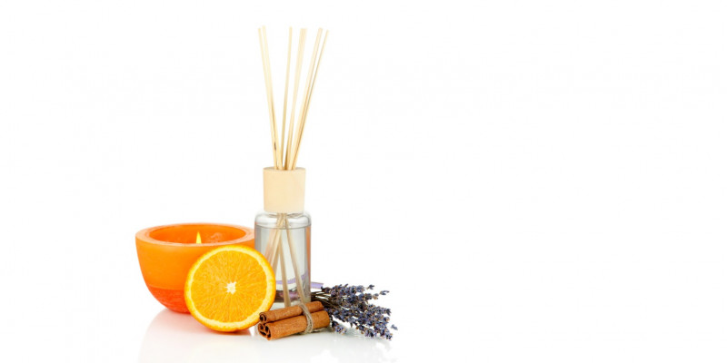 an orange perfumed candle, open bottle with fragrance and timber slats, an half orange, lavender and cinnamon sticks