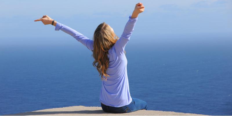 eine Frau sitzt am Meer und atmet tief durch, bis zum Horizont ist nur blaues Wasser zu sehen