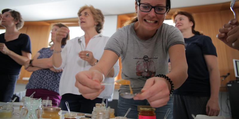 eine Gruppe Frauen vor einem Tisch mit Honiggläsern, eine junge Frau entnimmt Honig mit einem Teelöffel