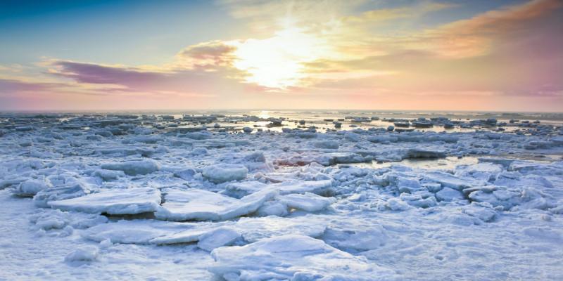 Eisschollen auf dem Meer, im Hintergrund färbt die tief stehende Sonne die Wolken am Horizont rosa