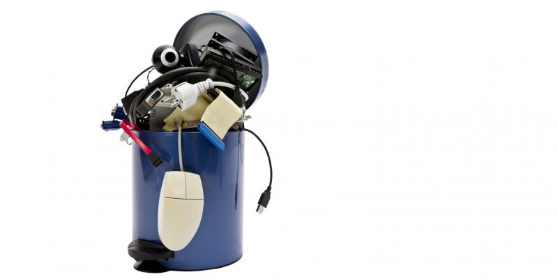 Elektronikschrott wie Computerbauteile und eine Computer-Maus quellen aus einem kleinen Mülleimer