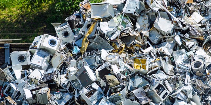 auf einem Wertstoffhof stapeln sich alte Waschmaschinen