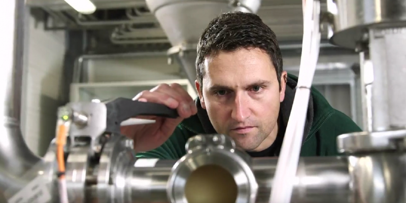 Ein Mann prüft eine Maschine in einer Werkshalle