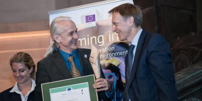 zwei lächelnde Männer vor einem Plakat mit der EU-Flagge, der eine hält ein gerahmtes Zertifikat in den Händen
