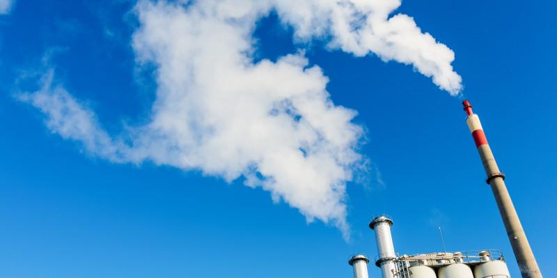 rauchende Schornsteine einer Industrieanlage vor blauem Himmel