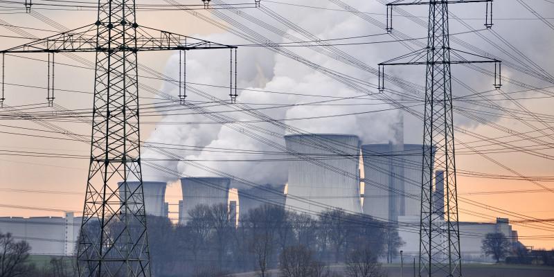 dampfende Kühltürme eines Kraftwerks und Hochspannungsleitung