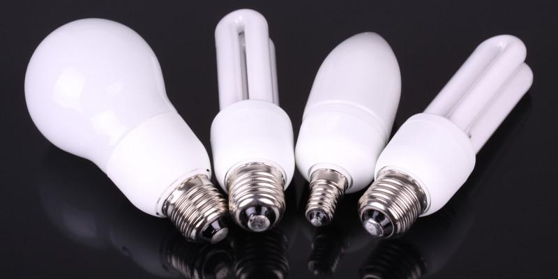 Zwei LED- und zwei Kompaktleuchtstofflampen auf einer schwarzen Oberfläche