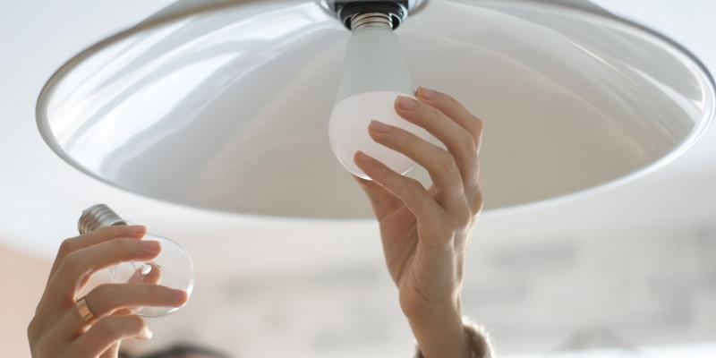 eine Frau tauscht eine Glühbirne gegen eine LED-Lampe aus