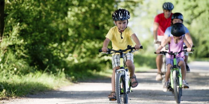 ein Mann und drei Kinder (alle mit Fahrradhelm) fahren in grüner Umgebung Fahrrad